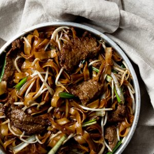 Beef Chow Fun (Beef Ho Fun) in a metal bowl with a handkerchief on the side