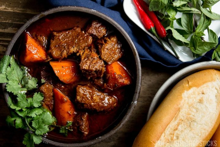 A large bowl of bo kho served with a side of Vietnamese baquette and basil