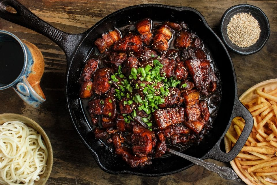 Chinese style beer braised pork belly in a cast iron pan served with fries and noodles