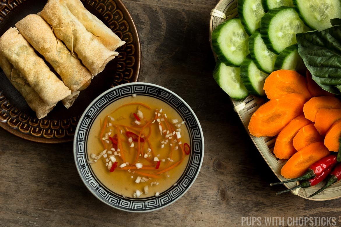 Vietnamese Fish Sauce Dipping Sauce (Nuoc Cham / Nuoc Mam) dipping sauce on a table with vegetables and spring rolls
