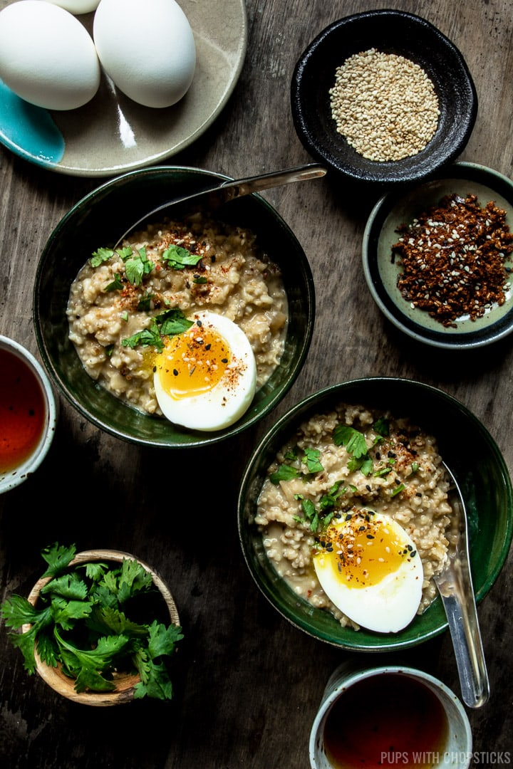 Two bowls of savory oatmeal with soft boiled eggs on top, served with small bowls of garnishes