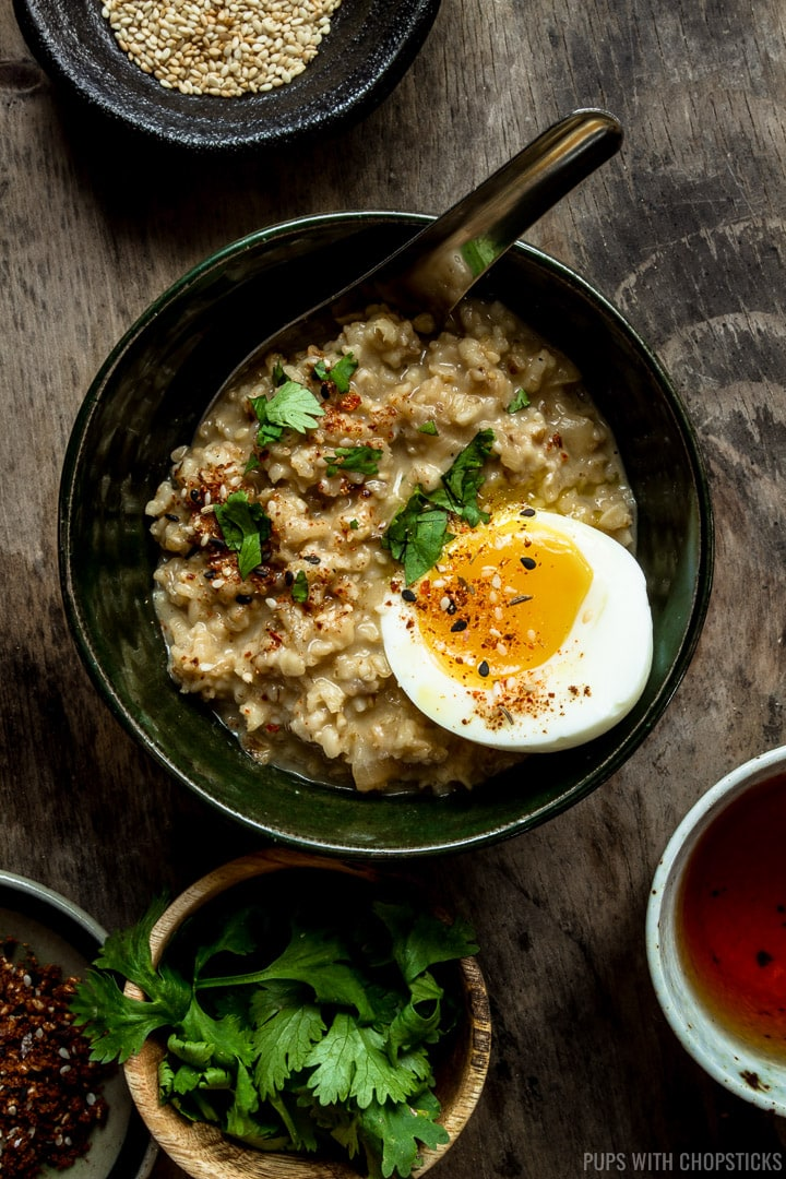 A bowl of savory oatmeal served with a soft boiled egg on top with garnishes on the table