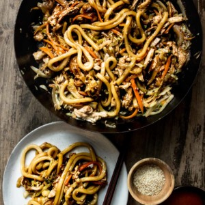 A pan with Stir Fry Chicken Teriyaki Noodles, being served on a plate with sesame seeds