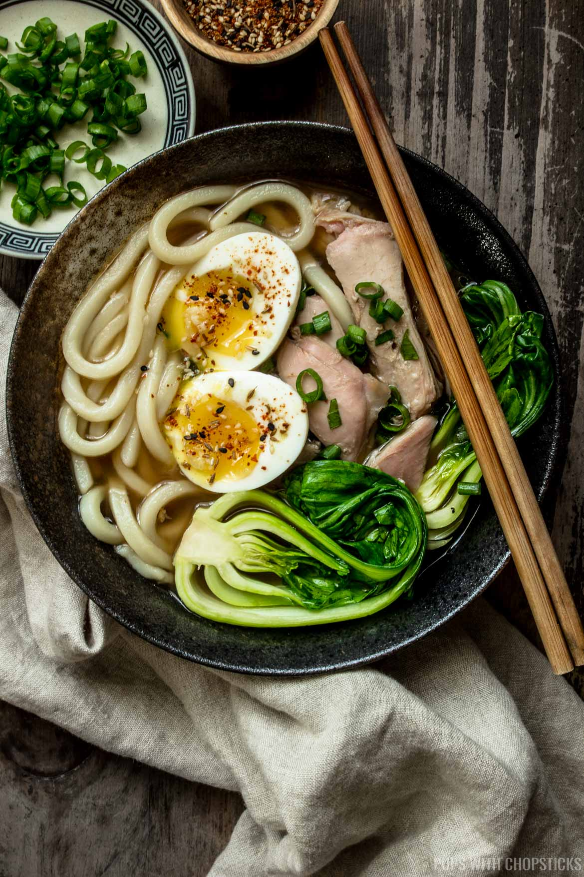 A large bowl of turkey udon noodle soup with soft boil egg, leftover turkey and bok choy on top, with green onions on the side.